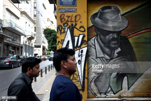 Two men walk in front of a graffiti in Athens Greece May 12 2017
