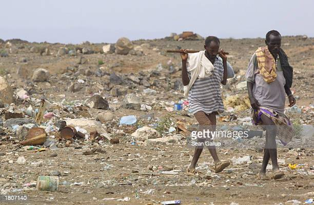 Two men walk near the BaalBalla slum February 21 2003 in the outskirts of Djibouti Town Djibouti BaalBalla is one of many Djibouti slums swollen by...