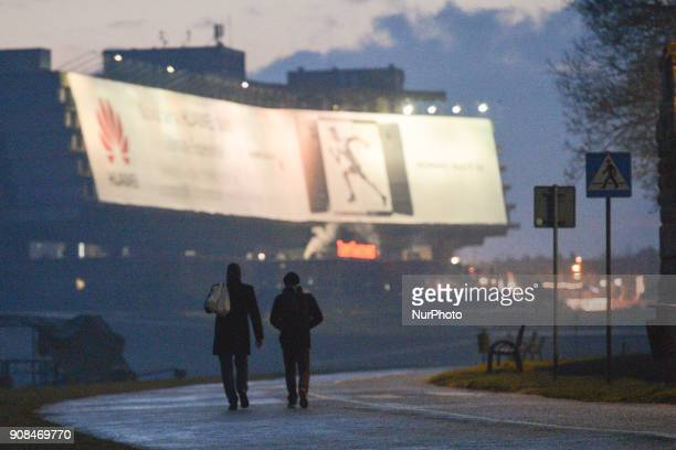 Two men walk near Vistula river with a view of the former Hotel Forum On Sunday 21 January 2018 in Krakow Poland
