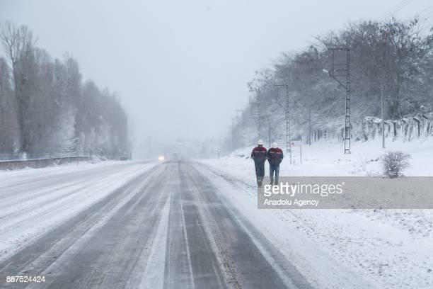 Two men walk on a roadside covered with snow in Van Turkey on December 07 2017