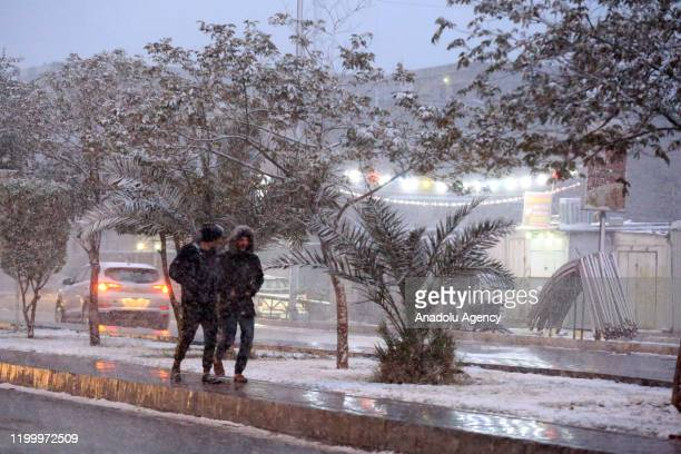 Two men walk on a side walk during snowfall in Baghdad, Iraq on February 11, 2020.