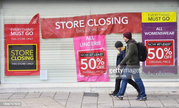 Two men walk past a closed Debenhams retail shop on March 12, 2021 in Stockport, England.