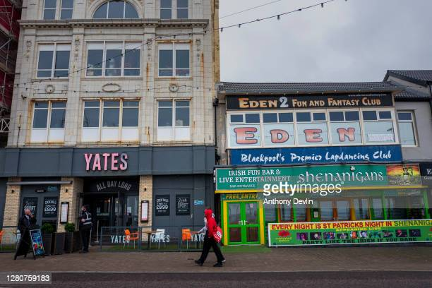 Two men walk past a closed pub and a Yates, which remains open to serve food, on the seafront on October 17, 2020 in Blackpool, England. Lancashire...