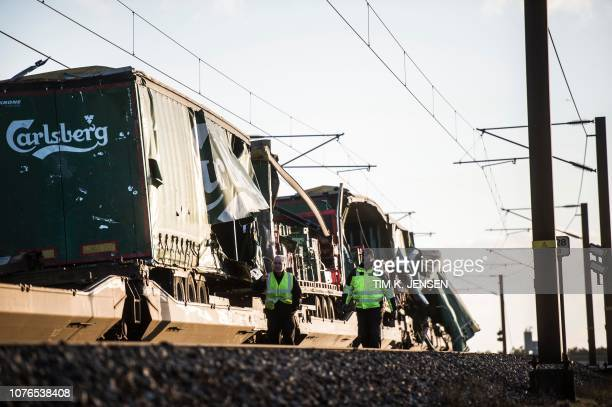 Two men walk past a damaged cargo train after an accident on January 2 2019 in Nyborg Denmark Several people were killed in a train accident on a...