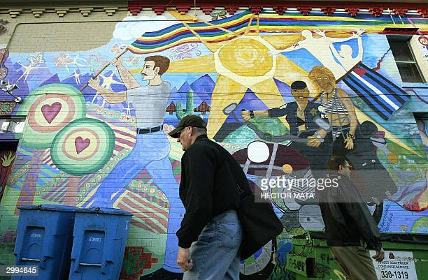 Two men walk past a mural in Castro the gay and lesbian neighborhood in San Francisco 18 February 2004 San Francisco's Mayor Gavin Newson has...