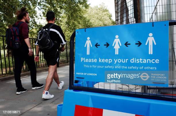 Two men walk past a sign reminding people to observe social distancing on Park Lane in London, England, on May 18, 2020. Britain began its ninth week...