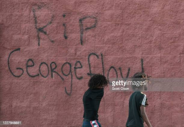 Two men walk past a wall that has RIP George Floyd written on it during a protest May 28 2020 in St Paul Minnesota Today marks the third day of...