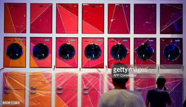 Two men walk past an installation of washing machines and fridges on display at the booth of Vestel as preparations are under way for the consumer...