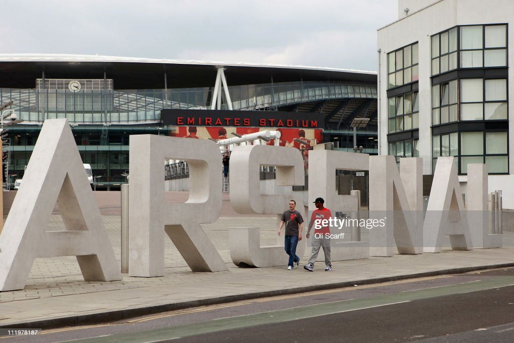 Two men walk past the sign for Arsenal Football Club's Emirates Stadium on April 11, 2011 in London, England. American businessman Stan Kroenke's company 'Kroenke Sports Enterprises' has increased its shareholding in Arsenal to 62.89% and will make an offer for a full takeover of the club. Mr Kronke first purchased 9.9% of Arsenal shares in 2007, today's deal values the Premier League club at 731m GBP.
