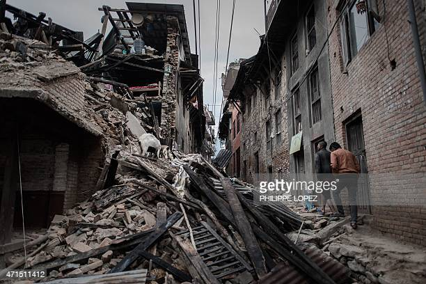 Two men walk past the wreckage of a building in Khokana a village dating back hundreds of years on the outskirts of Kathmandu on April 29 following a...