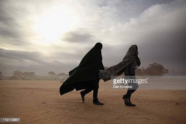 Two men walk through a United Nations displacement camp during a huge sandstorm on March 15 2011 in Ras Jdir Tunisia As fighting continues in and...