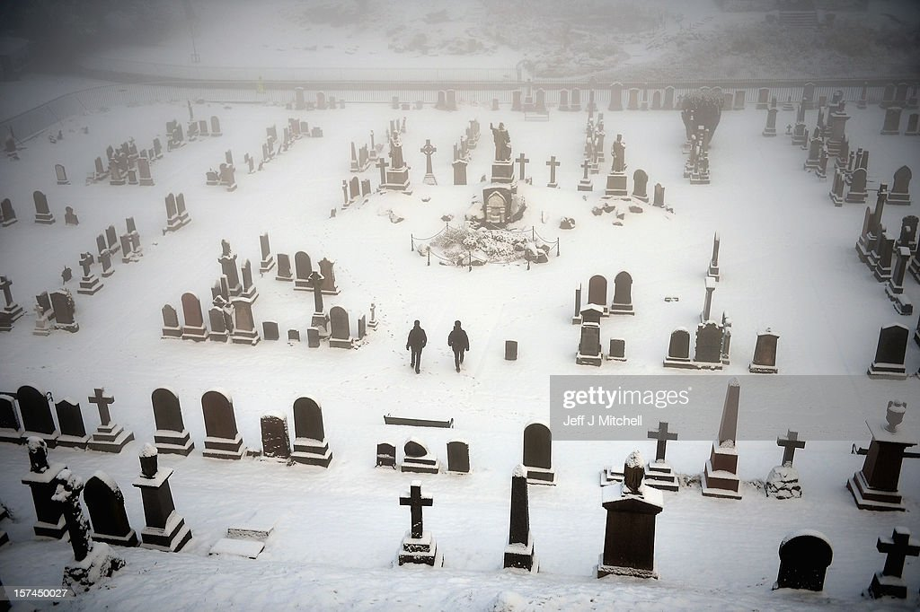 Two men walk through Stirling Castle graveyard on December 3, 2012 in Stirling, Scotland. Snow and sleet has hit many parts of Scotland with heavier falls expected over higher grounds.