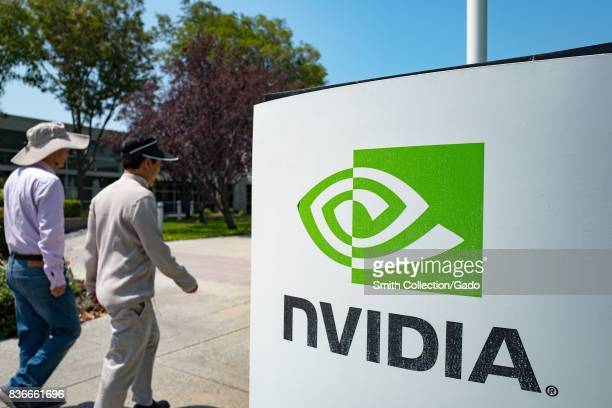 Two men walk together past signage with logo at the Silicon Valley headquarters of computer graphics hardware company Nvidia Santa Clara California...