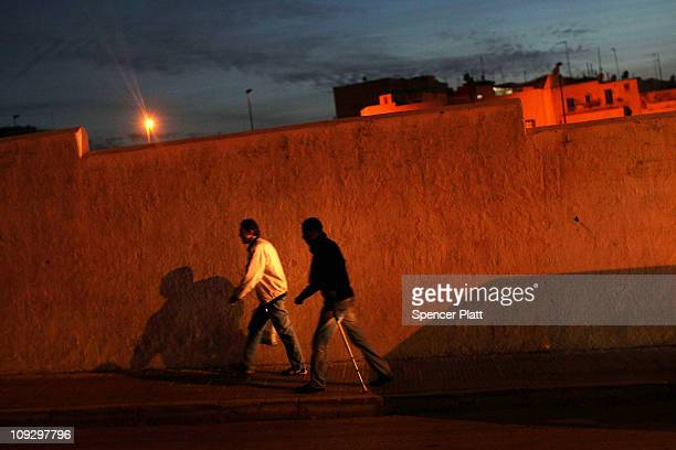 Two men walk up a street on February 19 2011 in Rabat Morocco Moroccan Facebook groups are calling for demonstrations this Sunday following the...