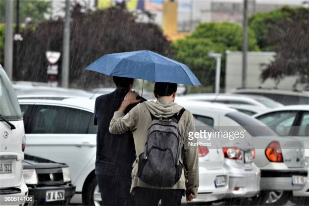 Two men walk with an umbrella outside a shopping mall during heavy rainfall in the spring season in Ankara Turkey on Sunday May 20 2018