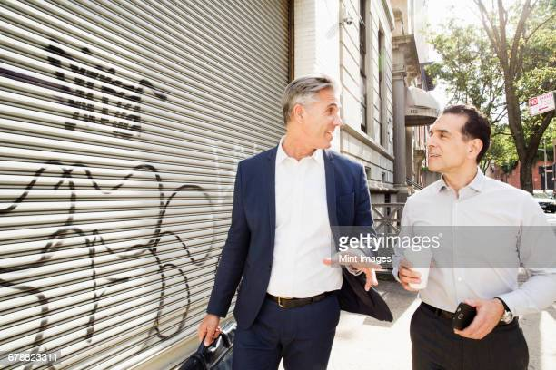 Two men walking along a street past a steel shutter on a building, painted with graffiti.