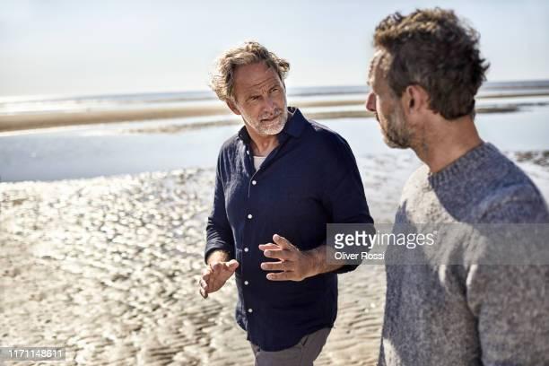 two men walking and talking on the beach - nur männer stock-fotos und bilder