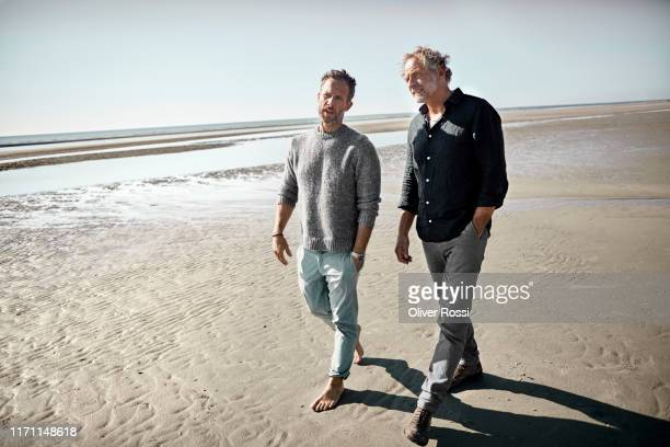 two men walking and talking on the beach - mature men stock pictures, royalty-free photos & images