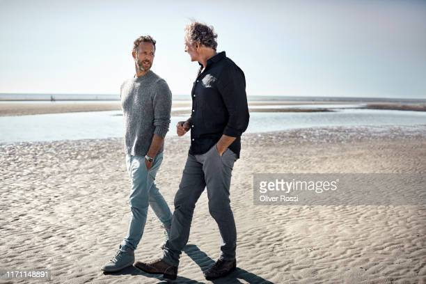 two men walking and talking on the beach - seulement des hommes photos et images de collection