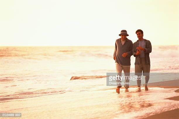 Two men walking at shoreline on beach