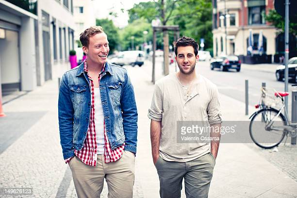 Two men walking down city sidewalk