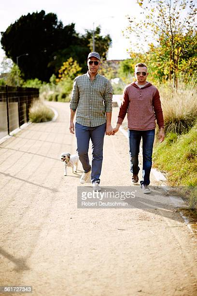 Two men walking hand-in-hand with their dog.
