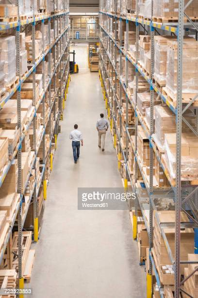 two men walking in factory warehouse - vertikal stock-fotos und bilder