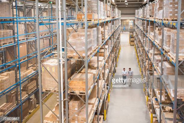 two men walking in factory warehouse - wide angle stock pictures, royalty-free photos & images