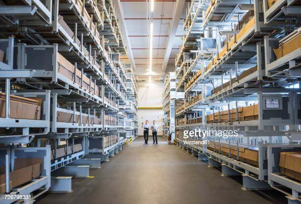 two men walking in factory warehouse - vanishing point stock pictures, royalty-free photos & images