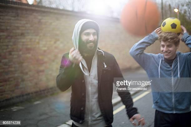 Two men walking in street, holding football