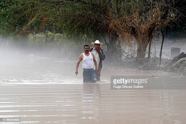 Two men walking on a submerged sidewalk following a heavy storm that left at least 90 homes flooded. At least 90 houses were flooded, 12 vehicles...