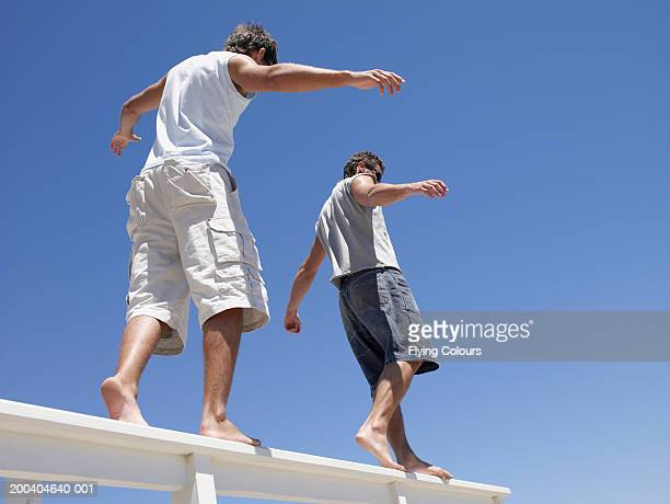 Two men walking on banister, low angle view