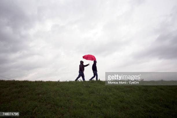 two men walking on grassy field against cloudy sky - umbrella stock photos and pictures