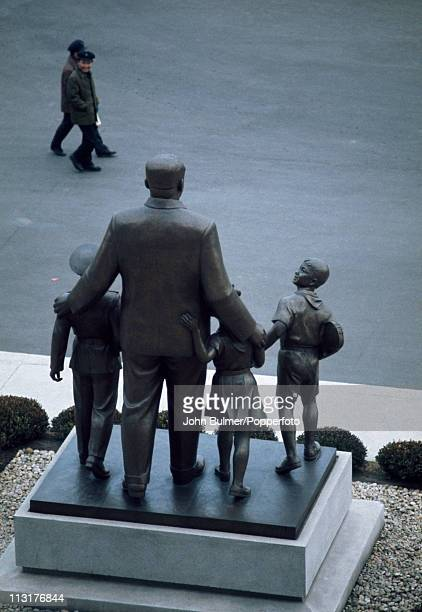 Two men walking past a statue of North Korean Communist leader Kim Ilsung with a group of children North Korea February 1973