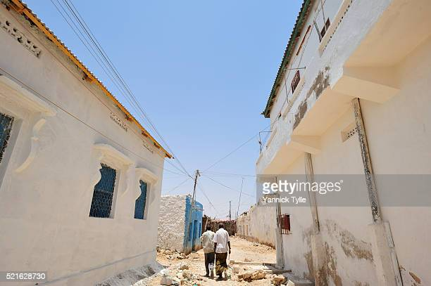 two men walking through a tight street in bosaso - bosaso stock pictures, royalty-free photos & images