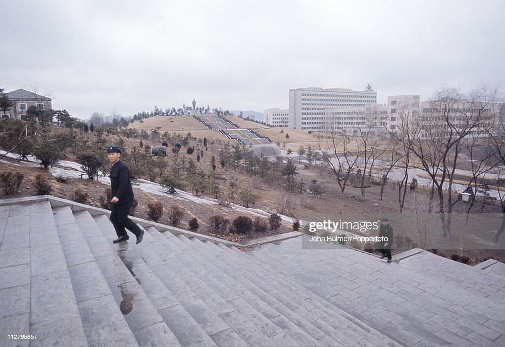 Two men walking up a flight of steps, North Korea, February 1973.