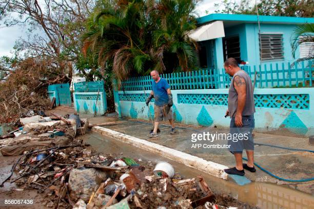 Two men wash away mud and debris from the front of their house in the aftermath of Hurricane Maria in Arecibo Puerto Rico September 30 2017 US...