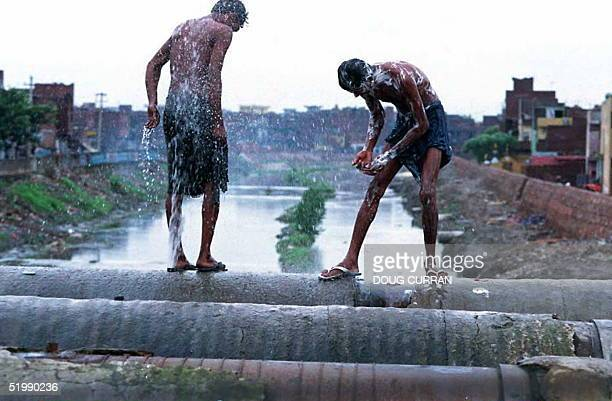 Two men wash themselves with water from a burst in a large water pipe above a canal beneath monsoon clouds 29 August in the Shahadra section of New...