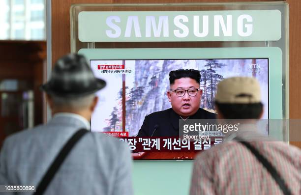 Two men watch a television screen showing a broadcast featuring North Korean leader Kim Jongun attending a news conference with South Korean...