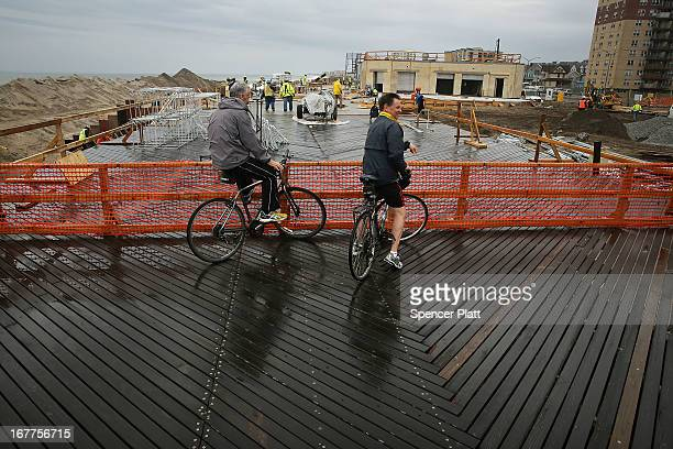 Two men watch as workers repair part of the Rockaway boardwalk which was heavily damaged in Hurricane Sandy on April 29, 2013 in the Queens borough...
