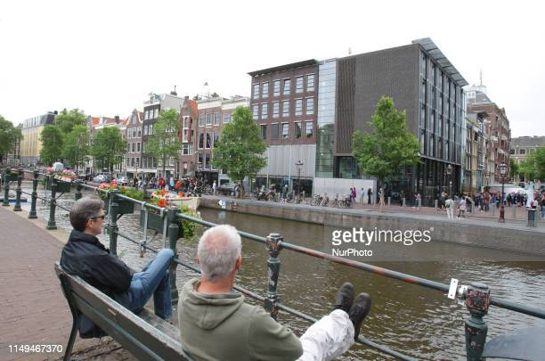 Two men watch at the Prinsengracht canal the Anne Frank house and museum remembering Anne Frank's 90th Birthday on June 12 2019 in...