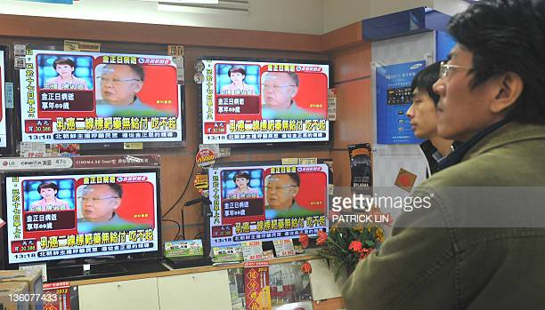 Two men watch television at a store in downtown Taipei on December 19 2011 as a local TV news channel broadcasti the death of North Korean leader Kim...