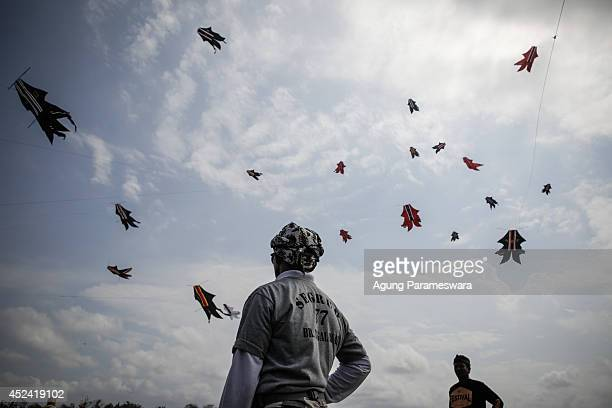 Two men watch traditional kites named Bebeban flying in the sky during the Bali Kite Festival on July 20 2014 in Denpasar Bali Indonesia The event is...
