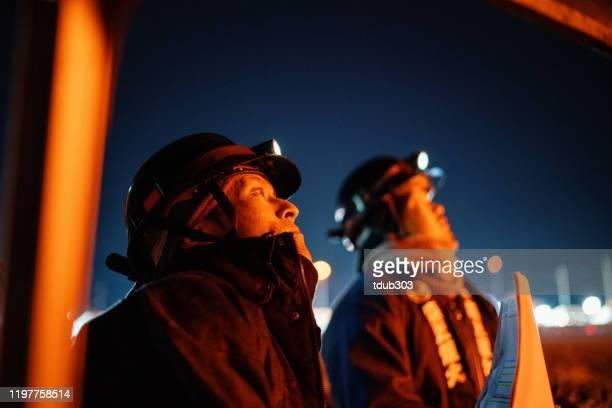 お祝いのイベントやフェスティバルの間に打ち上げた花火を見ている2人の男性 - 伝統 ストックフォトと画像