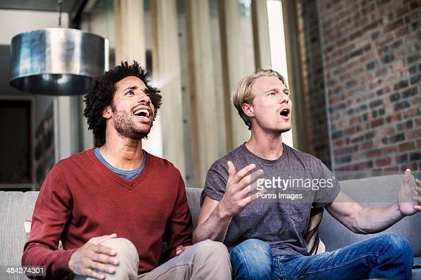 Two men watching sports on tv