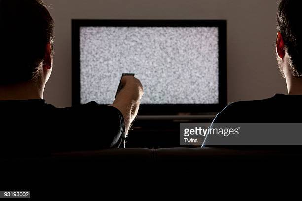 Two men watching static on television