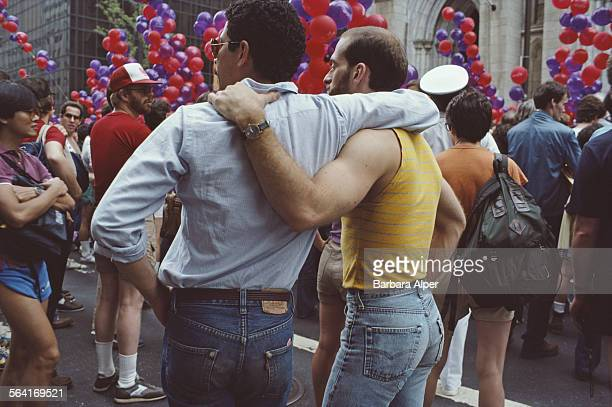 Two men watching the Gay Pride parade in New York City USA June 1984