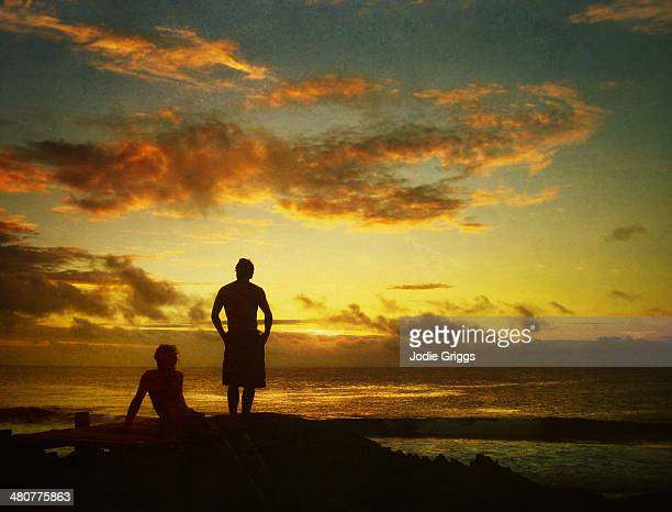 two men watching the sun set over the ocean - only young men stock pictures, royalty-free photos & images