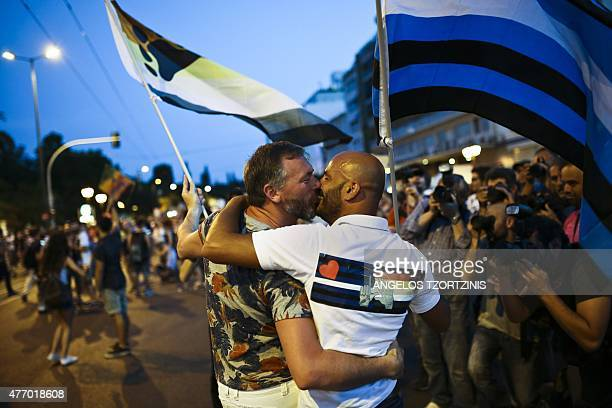 Two men waving flags kiss during the annual Gay Pride parade in central Athens on June 13 2015 Greece's radicalleft government on June 10 proposed a...