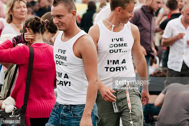 "Two men wear tank-top shirts proclaiming ""I've come out...I'm a Tory!"" at Brighton LBGT Pride."